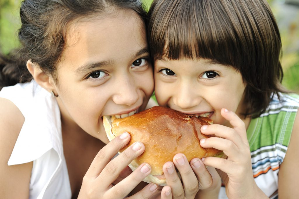 Closeup of two children eating sandwich in nature together, healthy food, care and love