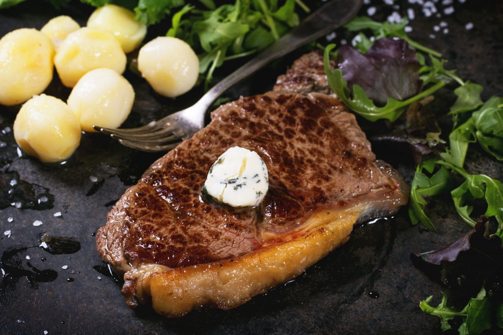 Grilled steak with butter, potatoes and green salad over black metal board